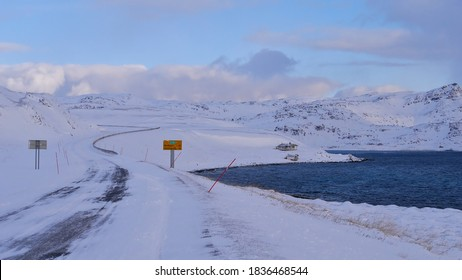 Icy road E69 with road sign displaying distance to Nordkapp (45km) near Honningsvåg, Norway, Scandinavia with red snowplow markings, remote house, snow-covered landscape and arctic sea in winter time.