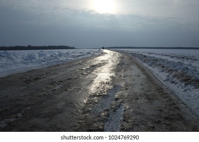 The icy road glistening under the rays of the sun is leaving into the distance.