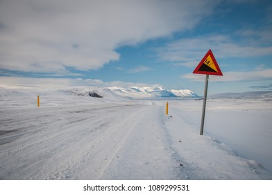 Icy road in north Iceland with sign, winter