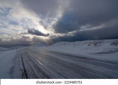 Icy road and snow-covered mountains leading to sea in winter Iceland with stormy sky