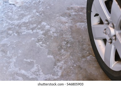 icy road surface during winter, with part of car wheel to the right.