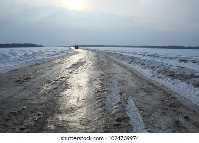 Icy snow-covered road, along which the dump truck moves.