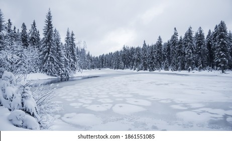 Icy winter at frozen pond. Snowy landscape. Blatny Water Reservoir in Jizera Mountains, Czech Republic