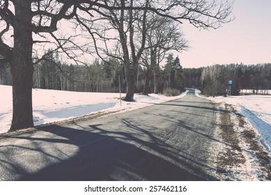 icy winter road with sun rays and trees - retro vintage effect