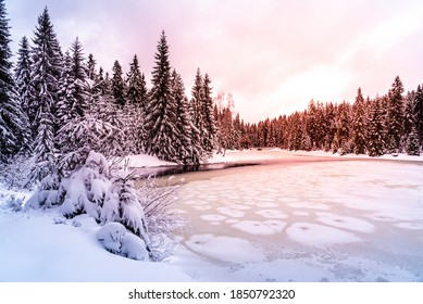 Icy winter sunset at frozen pond. Snowy landscape. Blatny Water Reservoir in Jizera Mountains, Czech Republuc