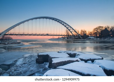 An icy winter sunset over Lake Ontario of the Humber Bay Arch Bridge.