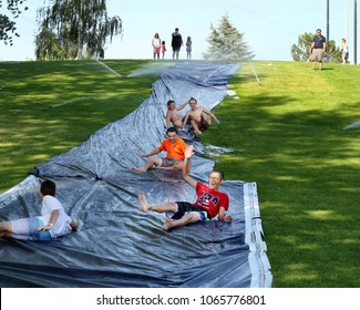 Idaho Falls, Idaho, USA  Aug. 4, 2016  A group of teenagers slide down a water soaked sheet of plastic, to cool off on a hot summer day at a public park.
