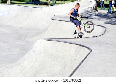 Idaho Falls, Idaho, USA Jul. 23, 2016 . A young boy (11-14) riding a bike in the bowl of a public skatepark, without a helmet, or safety equipment..