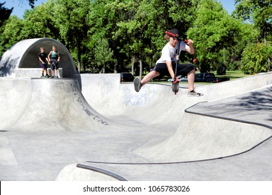 Idaho Falls, Idaho, USA Jul. 23, 2016 . A young boy riding a scooter in the bowl of a public skatepark, without a helmet, or safety equipment.