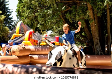 Idaho Falls, Idaho USA . Jul 4, 2016 A child enjoys the adrenaline rush while securely strapped a mechanical bull amusement ride at a Fourth of July festival in a mid sized city.