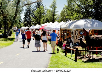 Idaho Falls, Idaho, USA July 23, 2016 Locals and tourists peruse the art works for sale at a sidewalk art sale in a mid sized us community.