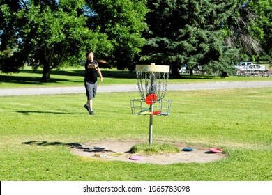 Idaho Falls, Idaho, USA  June 24, 2016  A man pratices throwing a frisbee at a target before a round of disc golf at a public park course.