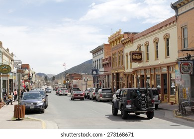 Idaho Springs, CO, USA - April 19, 2014: A sunny, commercial area of Miner Street where a lot of stores and shopping happens.Many people, vehicles and merchants line the downtown shopping area.