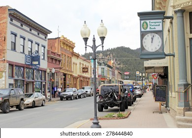 Idaho Springs, CO, USA - April 21, 2014: People shop in historical buildings stores, restaurants and more enjoying the spring day on Miner Street in downtown. Many old and colorful buildings