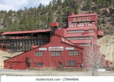 Idaho Springs, CO, USA - April 21, 2014: Large, red painted Argo gold mine and mill with a historical mining museum in front of a rising mountain. The Argo gold mine, mill and museum is a popular spot