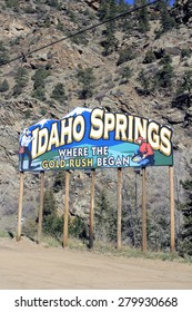Idaho Springs, CO, USA - April 23, 2014: Colorful billboard sign on the North side of Interstate 70 just before town that says, Idaho Springs Where the Gold Rush Began, with mining pick and panning