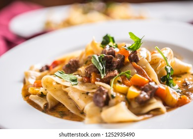 Idalian pasta pappardelle with beef ragout on white plate.