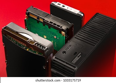 Ide, sata and usb connectors on external and internal hard drives to connect to a computer on a red background. History of the development of hdd. Storage technology.