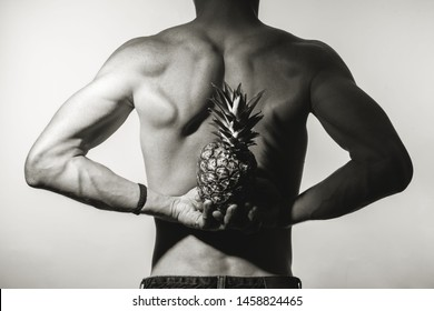 Idea of art of naturally handsome male body. The back of an athletic young man. He is posing with a naked torso on a gray background, holding a pineapple in his hands. Black and white studio shot