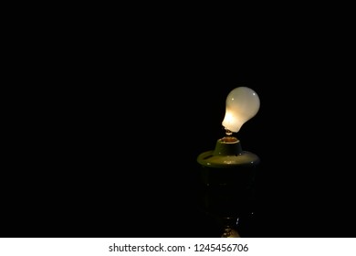 Idea bulb broken at base and still functioning on a dark black background with room of text.