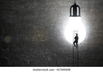 Idea concept with businessman climbing ladder to illuminated lightbulb on chalkboard background