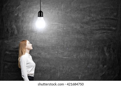 Idea concept with businesswoman looking up at ceiling lamp on chalkboard background