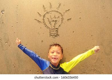 Idea concept. Cute boy laying on the beach and got idea.light bulb got the idea.