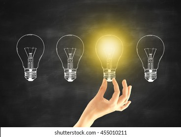 Idea concept with female hand holding abstract illuminated light bulb on chalkboard background
