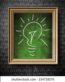 Idea concept light bulb chalkboard in old wooden frame on vintage wall