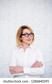 idea concept - mature business woman in eyeglasses looking up ant thinking about something over white brick wall with copy space