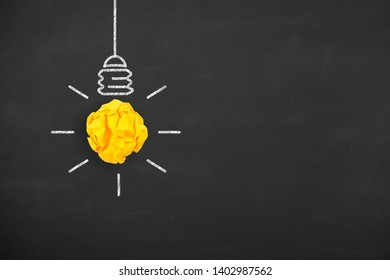 Idea Concepts Light Bulb with Crumpled Paper on Blackboard Background