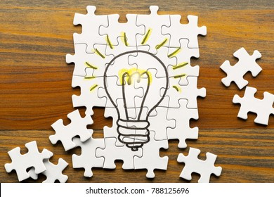 Idea creation. Light bulb drawn on puzzle.  Puzzle pieces on wooden desk.