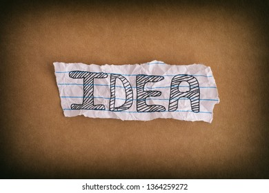 Idea. Crumpled piece of paper with the word Idea on brown paper background. Close up.