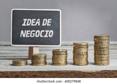 Idea de negocio, Spanish text for Business Idea, on black board behind growing stacks of money on wood table