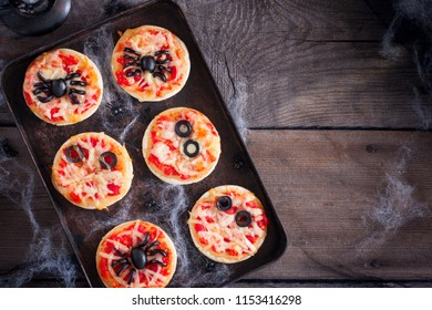 The idea of a festive meal for Halloween: mini pizza with spiders, mummy and spiderweb, copy space, top view