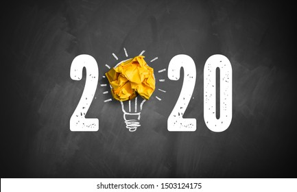 idea found for 2020 symbolized as a lightbulb out of crumpled paper on a blackboard