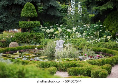 The idea of landscape design. Modern style. French style.Grass surrounds a small pond with a sculpted figure on the center. Exotic tree stands near the pond. Float on the pond water lilies.