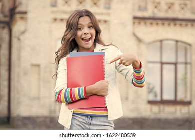 The idea made in book. Happy small child pointing finger at book with genius idea. Adorable schoolgirl got main idea of book. You get the idea.