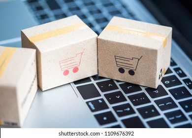 Idea of shopping online and service / e-commerce concept. Stack boxes on laptop for Customer can buy from electronic internet.