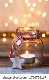 Idea for simple cozy handmade holiday home decor: glass jar, candle decorated with red ribbon. Christmas lights, homemade gingerbread cookies, wooden background. Close up macro, copy space for text