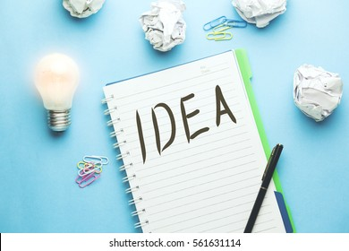 Idea text writeen on notebook with papers   and light bulb