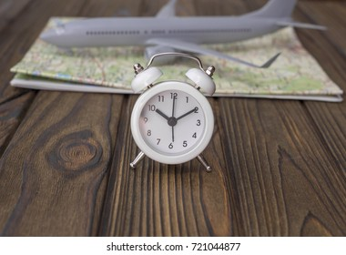 The idea: time to travel. Alarm clock, airplane on the map.
