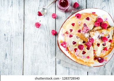 Idea for Valentine's Day surprise gift. Cute pancakes crepes with berry sauce and heart shaped cutouts. Romantic valentine breakfast. On wooden table, with fresh raspberries. Copy space