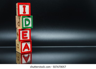 IDEA word wooden block arrange in vertical style on black background and selective focus