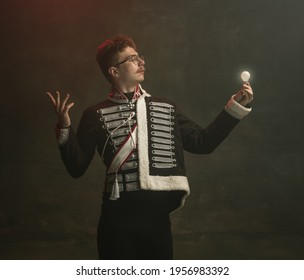 Idea. Young man in suit as royal person isolated on dark green background. Retro style, comparison of eras concept. Beautiful male model like historical character, monarch, old-fashioned. - Shutterstock ID 1956983392
