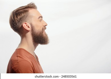 Ideal beard. Side view portrait of handsome bearded man wearing orange tshirt and smiling at copy space while standing against white background
