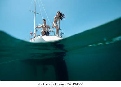 Ideal beauty young laughing couple on sailing yacht. Split with underwater, real shoot.