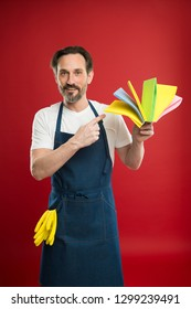 Ideal for cleaning. Eldery household worker presenting cleaning towels. Mature man pointing at cleaning cloths of assorted colors. Senior man in bib apron with rubber gloves. Household service.