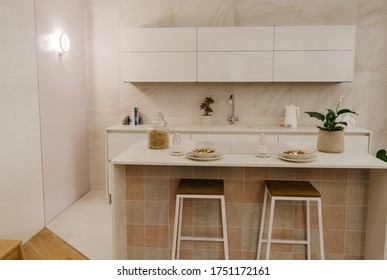 Ideal Home Show, London - June, 2019. Modern white kitchen clean interior design, breakfast on table