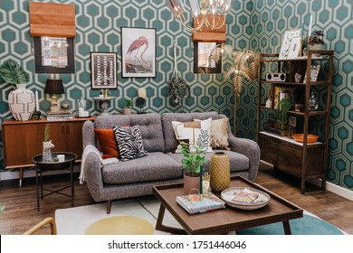 Ideal Home Show, London -  June 2019. Cropped shot of couch with pillows in living room with green wall.